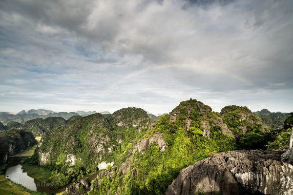 Cầu vồng trên đỉnh núi khi mặt trời mọc.